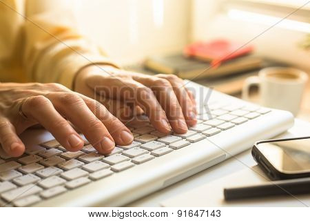 Female hands typing on a keyboard.