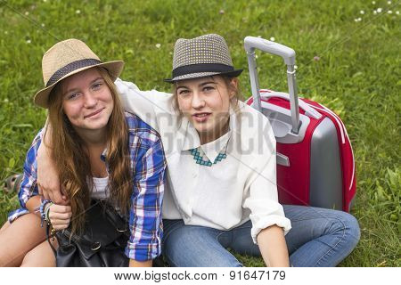 Two young girls girlfriends travellers, sitting on the grass.