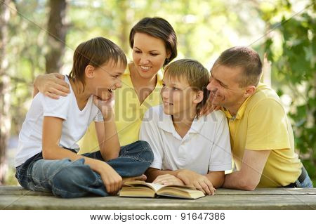 Family of four reading outdoors