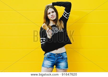 Outdoor fashion portrait of young hipster girl with  ice-cream on yellow wall background