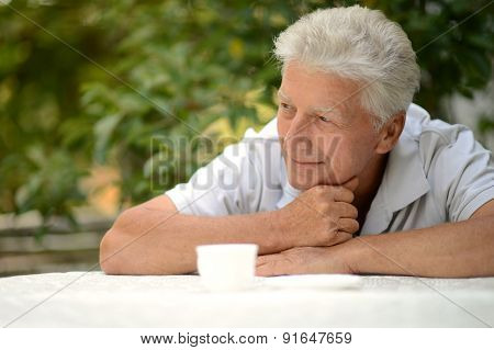 Elderly man with cup of coffee