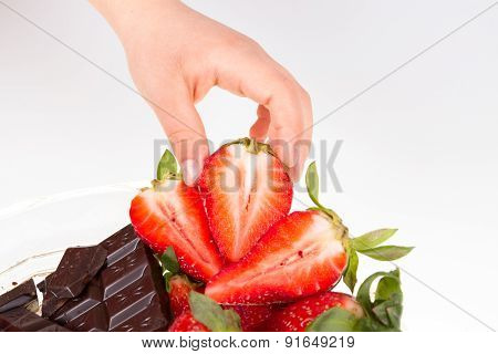 Child's hand picking strawberry