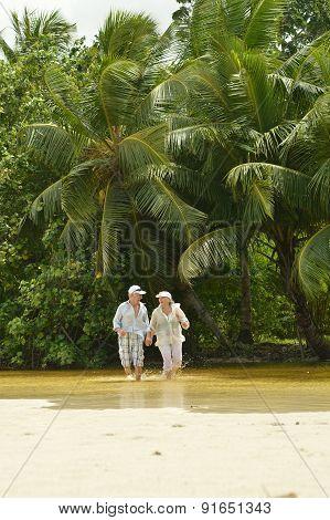 Elderly couple running on the beach