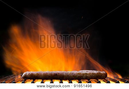 Delicious grilled sausages burning in fire, isolated on black background