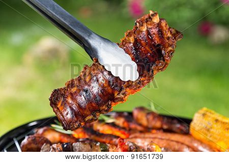 Delicious ribs in sticks placed above grill