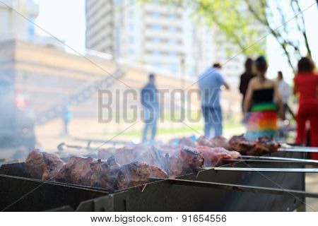 Closeup of barbecue with slices of meat on skewers in front of people
