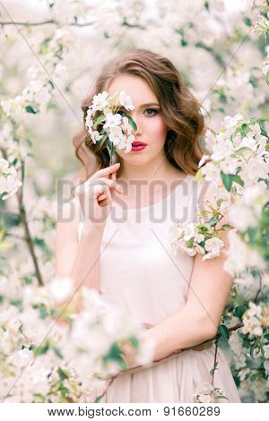 Portrait of beautiful woman in the flowering park