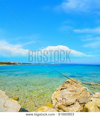 Fishing Rod On Yellow Rocks In Capo Testa