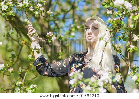 Beauty And Youth Lifestyle Concept: Portrait Of Young Caucasian Blond Woman Standing In Park By The