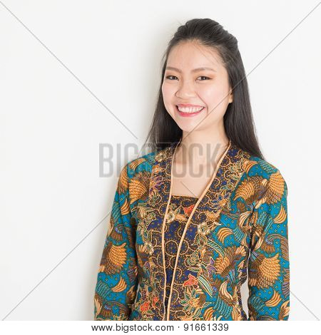 Portrait of Southeast Asian woman in batik dress on plain background.