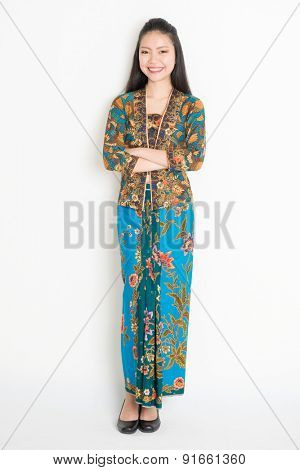 Full body Southeast Asian girl in batik dress standing on plain background.