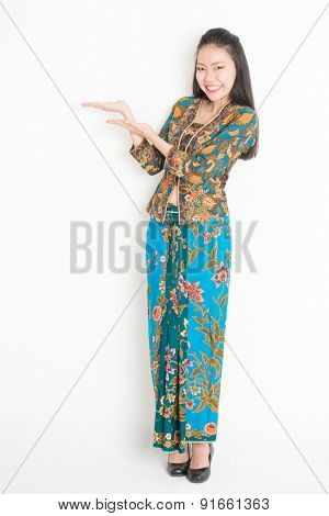 Full body portrait of Southeast Asian female in batik dress hand holding something standing on plain background.
