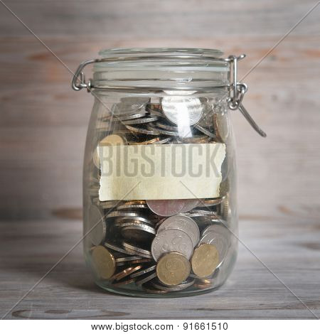 Coins in glass money jar with blank label, financial concept. Vintage wooden background with dramatic light.