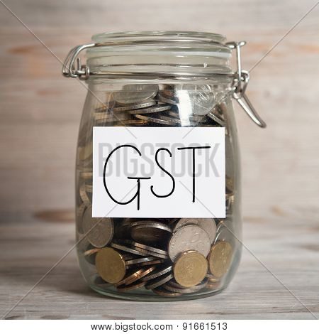 Coins in glass money jar with gst label, financial concept. Old wooden background with dramatic light.