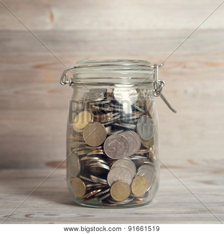 Coins in glass money jar, financial concept. Vintage wooden background with dramatic light.