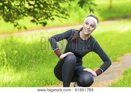 Portrait Of Young Fitwoman Resting Outdoors In The Park