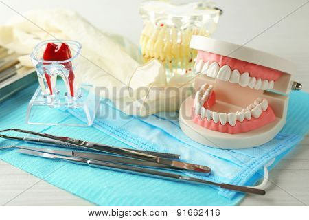 White fake teeth, prosthesis and dental instruments on table background