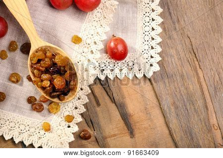 Raisins in wooden spoon with grapes on table close up