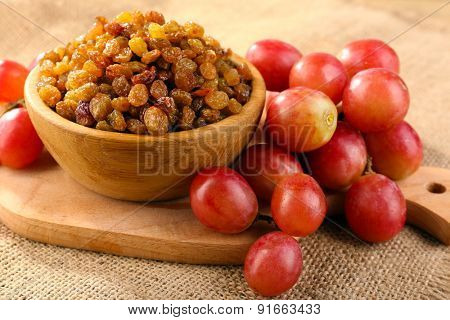 Raisins in bowl with grapes on table close up