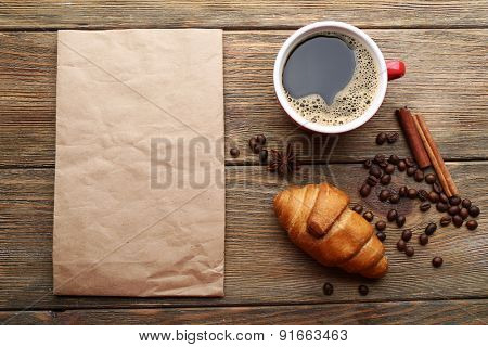 Cup of coffee and fresh croissant on wooden table, top view