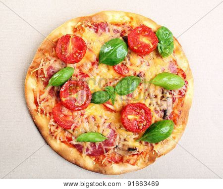 Tasty pizza with vegetables and basil in cardboard box close up