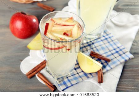 Glasses of apple cider with fruits on table close up