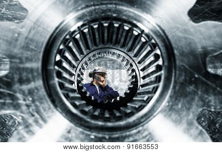 engineer, worker, seen through a large cogwheels axle, focus on the engineer