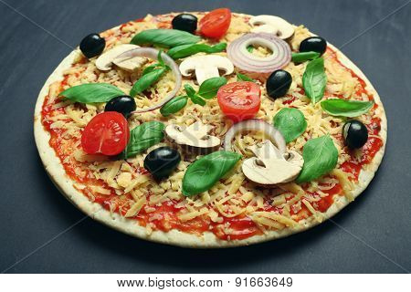 Raw pizza with vegetables on table close up