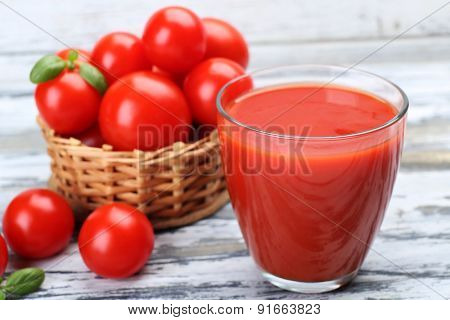 Glass of tomato juice with vegetables on table close up