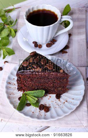 Delicious chocolate cake with mint and cup of coffee on table close up
