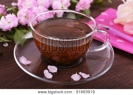 Cup of herbal tea with pink roses on wooden table, closeup