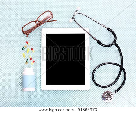 Medical tablet with stethoscope on blue background