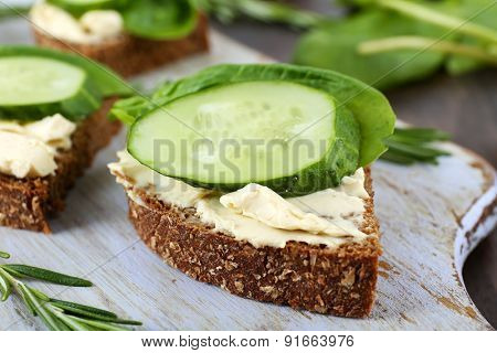 Delicious sandwiches with vegetables and greens on cutting board close up
