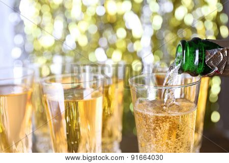 Pouring champagne from bottle into glasses on bright background