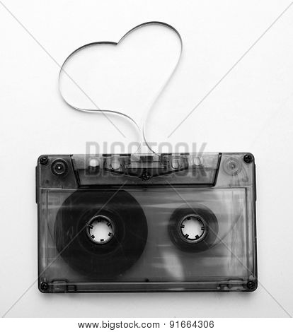 Audio cassette with magnetic tape in shape of heart isolated on white