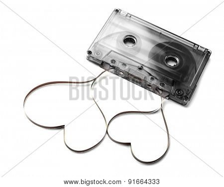 Audio cassette with magnetic tape in shape of hearts isolated on white