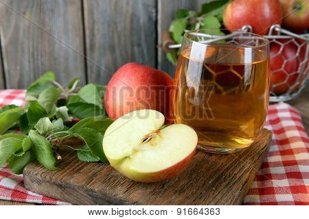 Glass of apple juice on wooden background