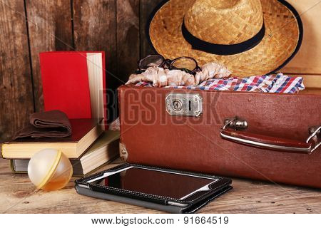Packing suitcase for trip on wooden background