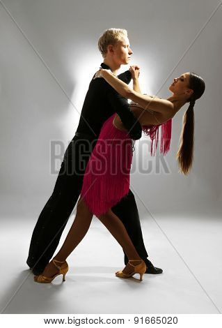 Beautiful couple of professional artists dancing on gray background
