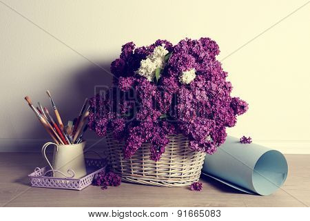 Beautiful lilac flowers on basket on floor in room close-up