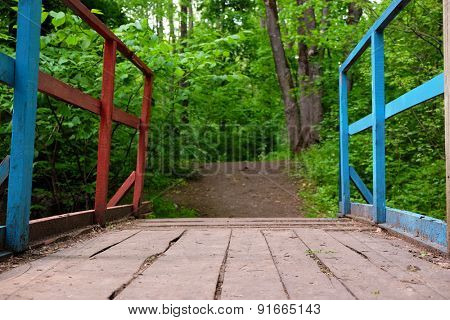 Wooden bridge in park over green trees background