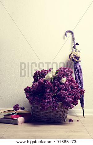 Beautiful lilac flowers with umbrella on floor in room close-up
