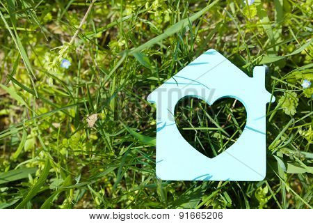 Toy house on grass background