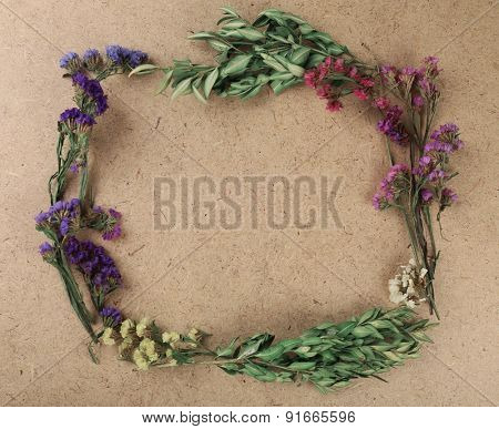 Wildflowers as frame on plywood background