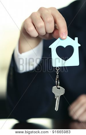 Portrait of businessman with keys in hand in office, closeup