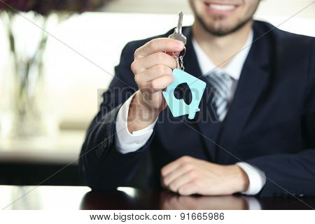Portrait of businessman with keys in hand in office on blurred background