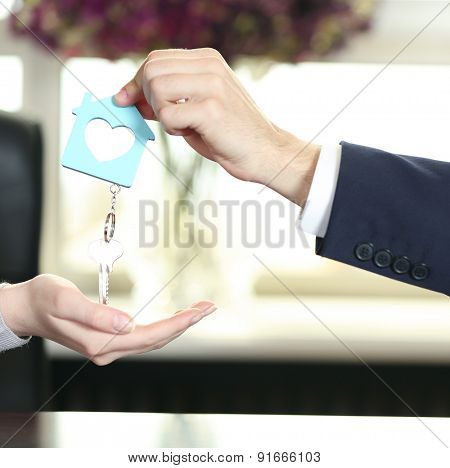 Hand of businessman giving keys to female hand on blurred background