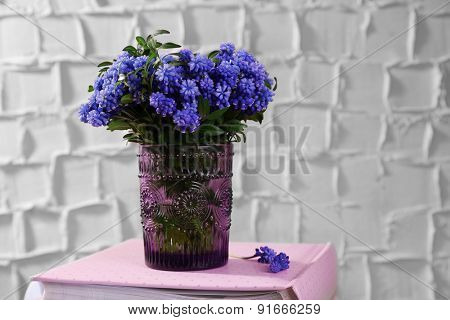 Beautiful bouquet of muscari - hyacinth in vase on wall background