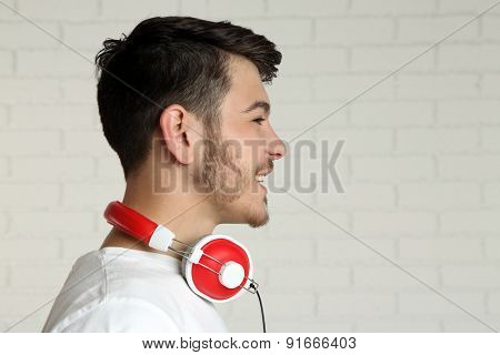 Handsome young man listening to music on brick wall background background