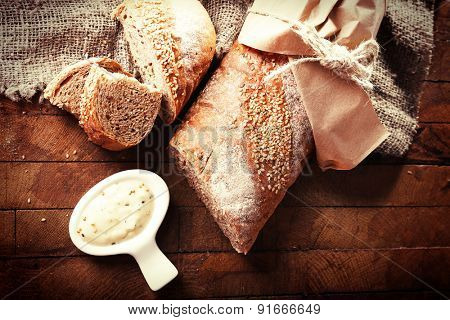 Fresh baked bread wrapped in paper and bowl with sauce, on wooden background